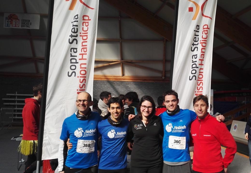 Photo de groupe de la team Mission Handicap Sopra Steria - FÉDÉEH devant les bannières de Sopra Steria